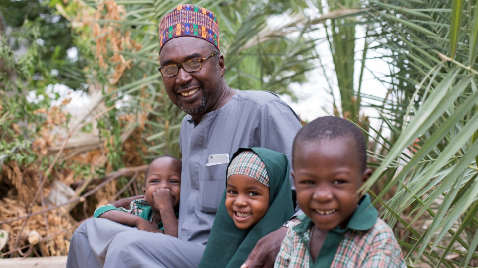 Mustapha and three of his children sit in the garden of his family home next to the first of two schools he set up for orphans and other children in conflict-battered Maiduguri, Borno State, Nigeria.