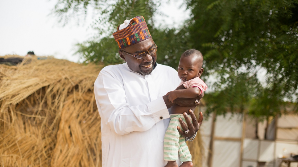 Mustapha holds baby Zannah who was named after him by displaced people living near the second of two schools he created in Maiduguri.