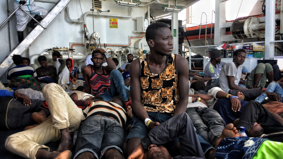 Refugees and migrants rest on the deck of Italian Coast Guard patrol vessel Dattilo.