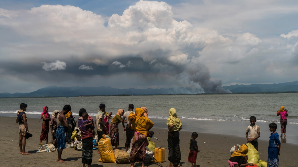 Rohingya families gather on the beach at Dakhinpara, Bangladesh, after crossing the sea on fishing boats from Myanmar.