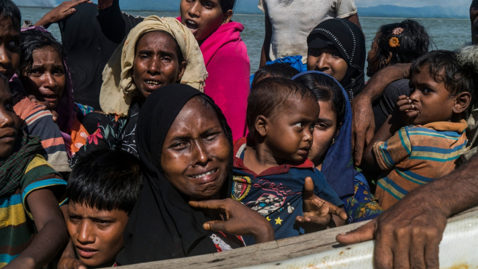 Rohingya women and children huddled on a fishing boat approach the beach at Dakhinpara, Bangladesh.