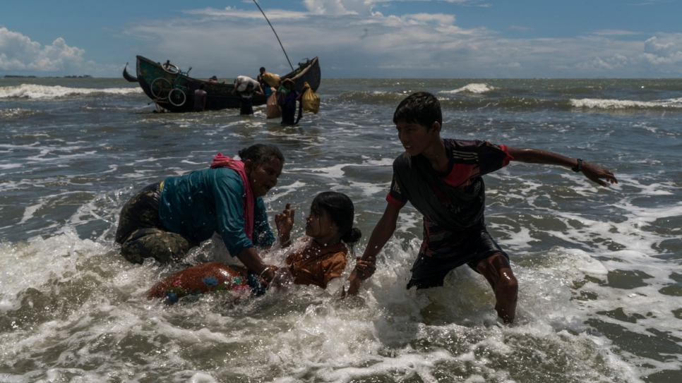 Rohingya refugees scramble off a fishing boat as it nears the beach at Dakhinpara, Bangladesh.