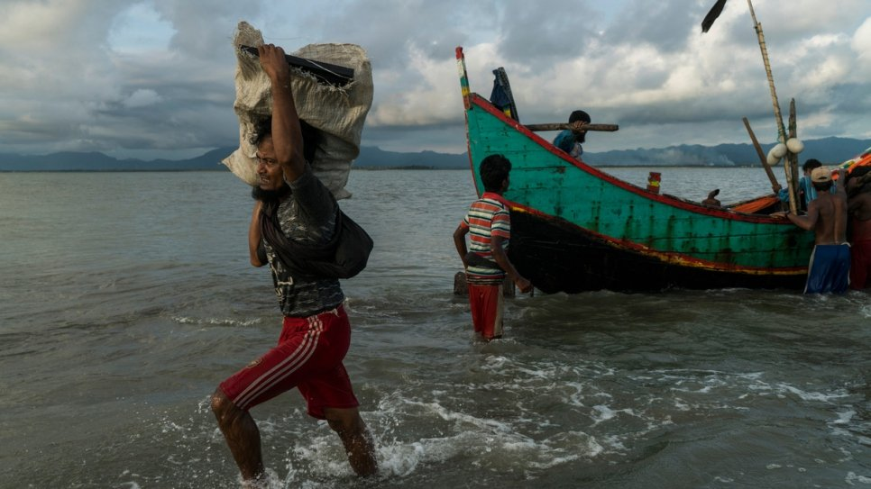 A Rohingya man carries a package towards the beach at Dakhinpara, Bangladesh.