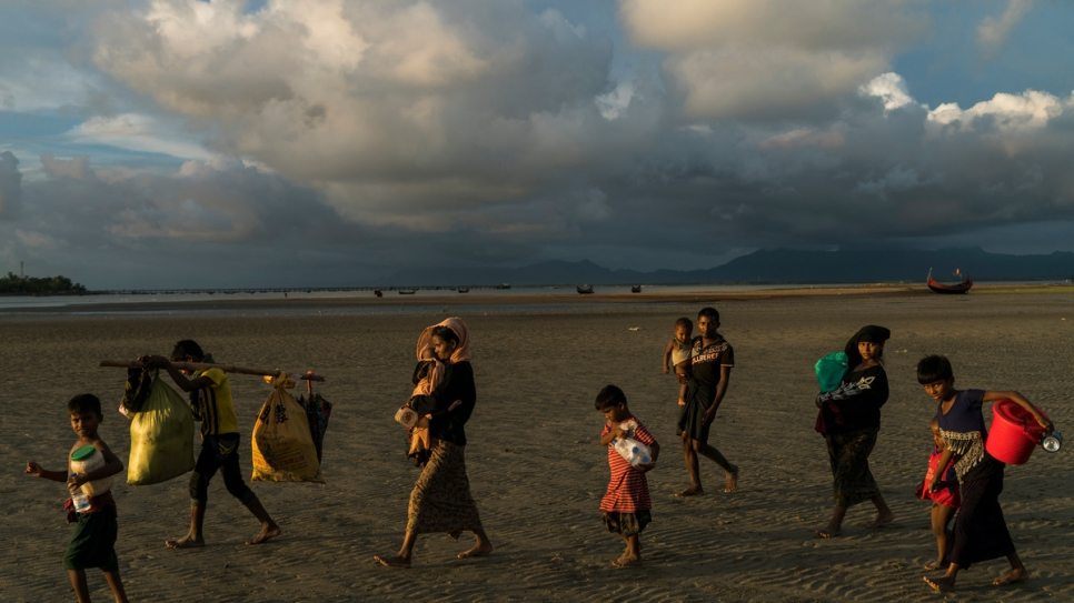 Rohingya families make their way across the beach at Dakhinpara, Bangladesh, after crossing the sea on fishing boats from Myanmar.