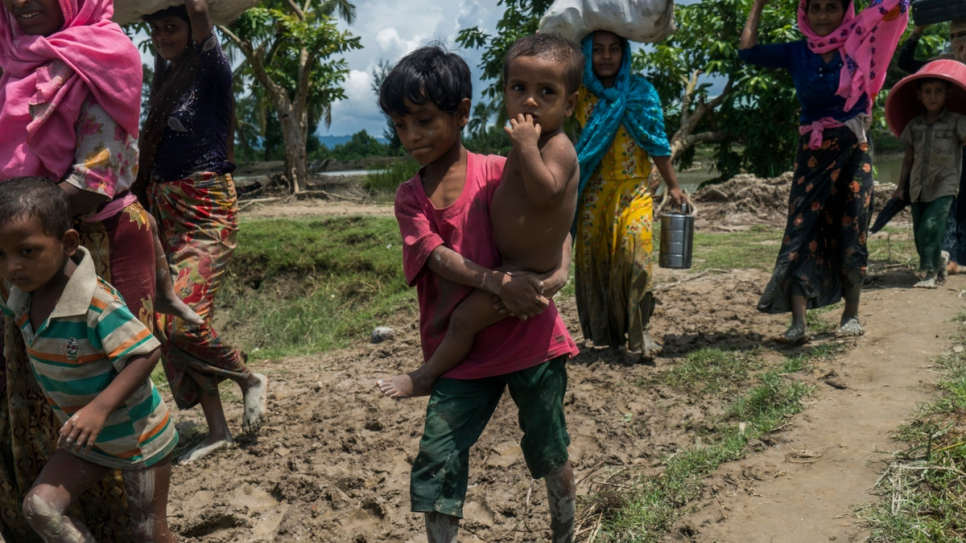 A Rohingya boy carries his little brother as he crosses with his family into Whaikhyang, Bangladesh.