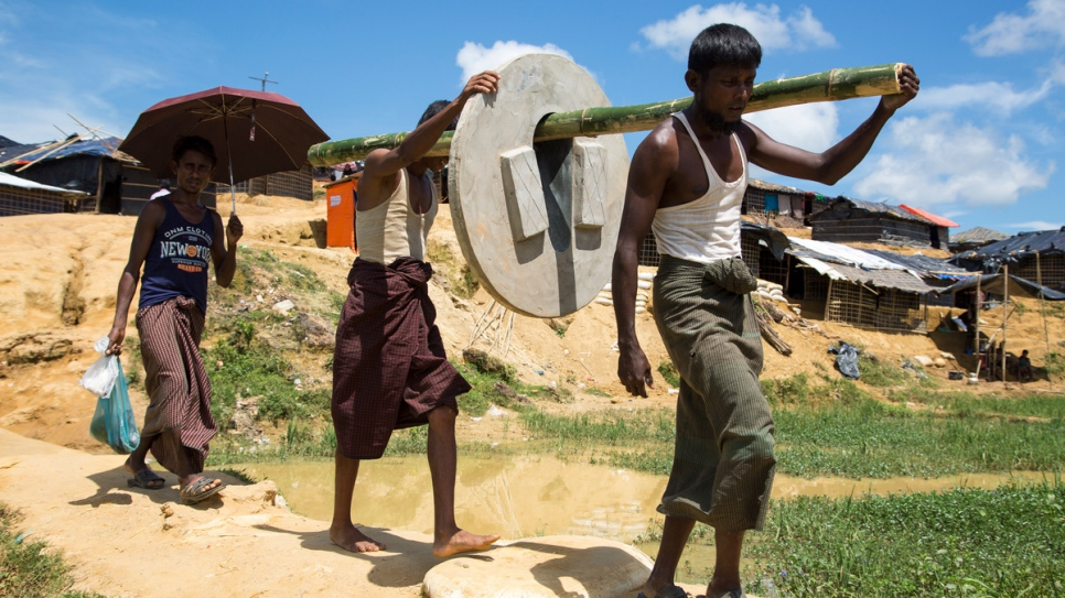 UNHCR's Bangladeshi partners take sections of concrete pipe to build latrines into the camp extensions on bamboo poles.