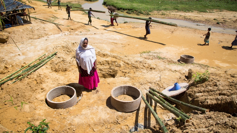 Abdula Hakim stands next to the field latrines being set up near her shelter.