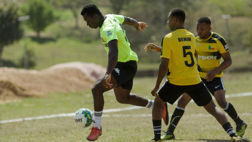 Benin (in yellow) and Togo (in green) clash in the first round of the Refugees World Cup at CERET Park, Sao Paulo, Brazil.