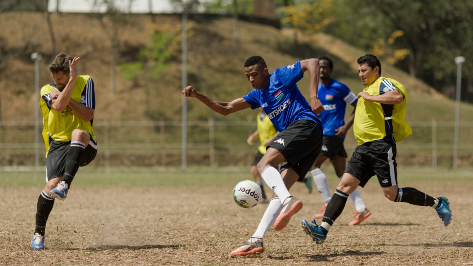 Colombia (in blue) and Gambia (in yellow) go head to head in a first round match at the Refugees World Cup in CERET Park, Sao Paulo, Brazil.