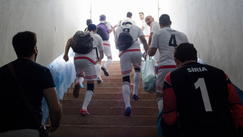 Syrian players run on to the pitch at the Refugees World Cup in CERET Park, Sao Paulo, Brazil.