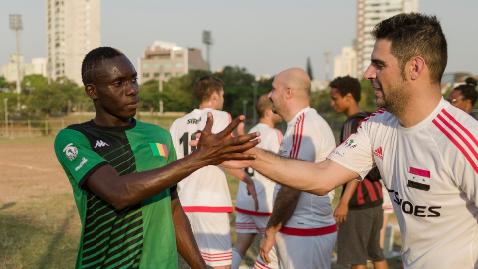 Syrian and Malian players shake hands after their Refugees World Cup game in CERET Park, Sao Paulo, Brazil.