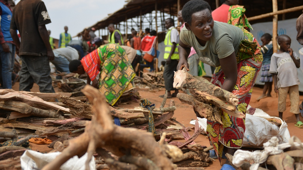 Charlene collects firewood for her family's new shelter at Mahama refugee camp.
