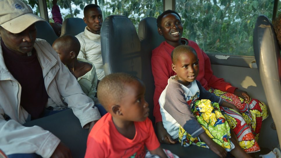 Charlene sits in a UNHCR-chartered bus along with her husband (behind) and their two children.
