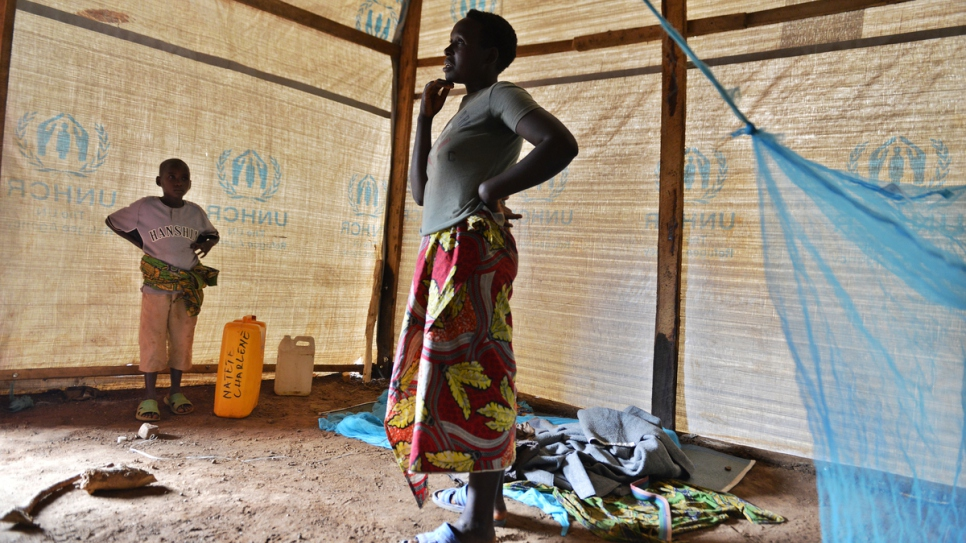 Charlene stands in her new shelter with her son at Mahama refugee camp.