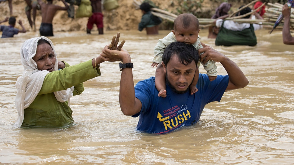 A family of Rohingya refugees from Myanmar crosses a river swollen by monsoon rains at Kutupalong, Bangladesh, during the 2017 monsoon season.