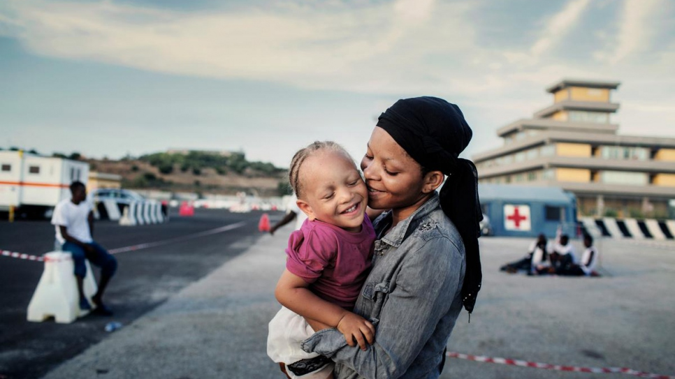 Nigerian refugee Shalom, 24, hugs her young daughter after being rescued at sea and taken to the Italian port of Augusta.