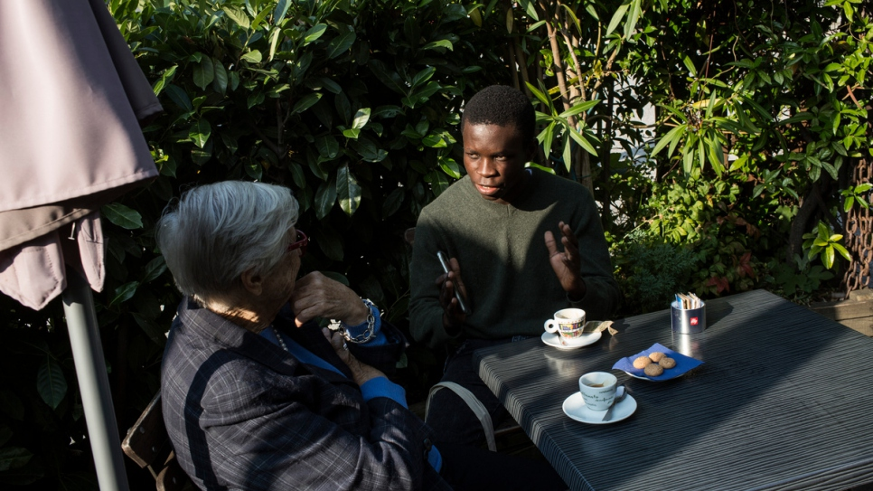 Emmanuel talks with Anna Illy at a cafè in in Duino. Anna donated him a full scholarship to attend the Adriatic College.