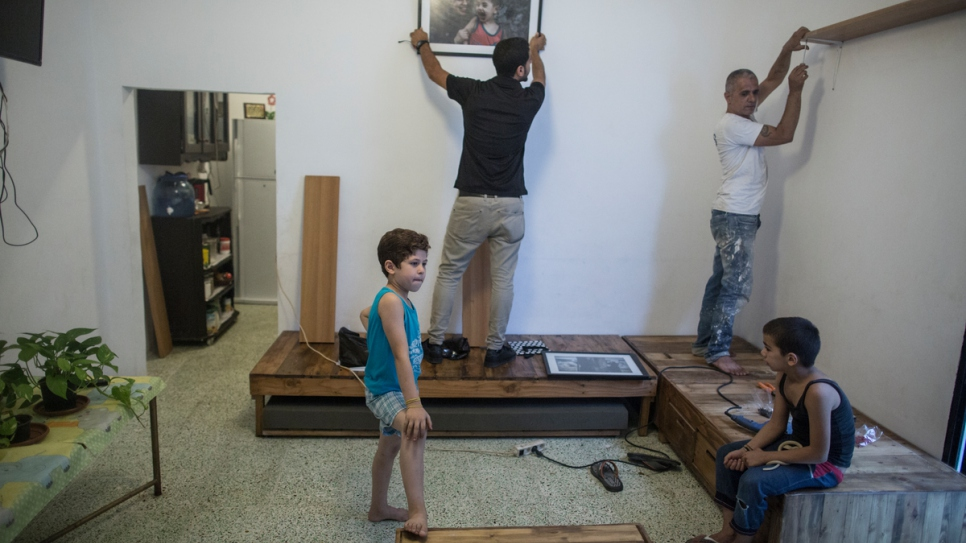 Decorators hang shelves and photographs in Haela's newly renovated home.