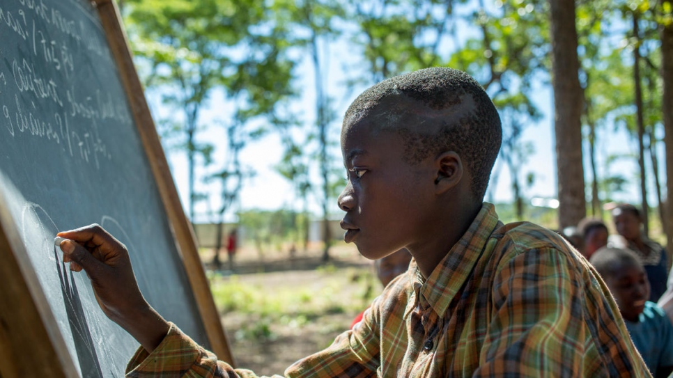 Burundi refugee student Richard Nduwimana, 13, writes on the blackboard.