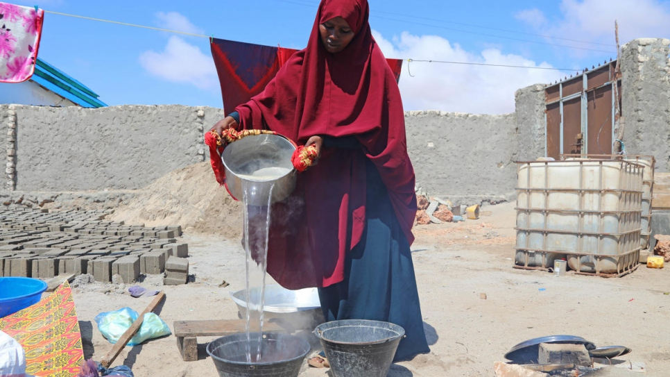 Without running water, Fadumo carries buckets back and forth to add water to her dyes.