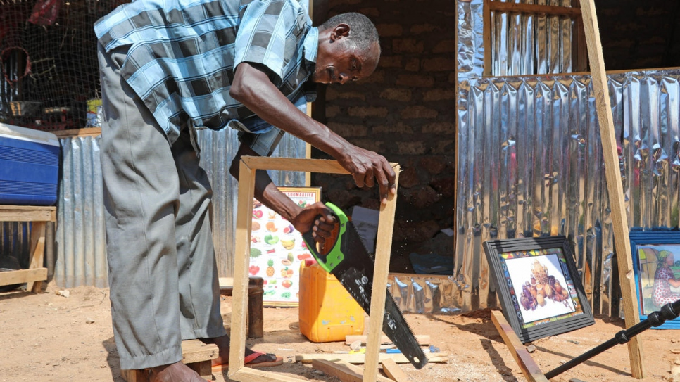 Mohamed constructs a wooden frame.