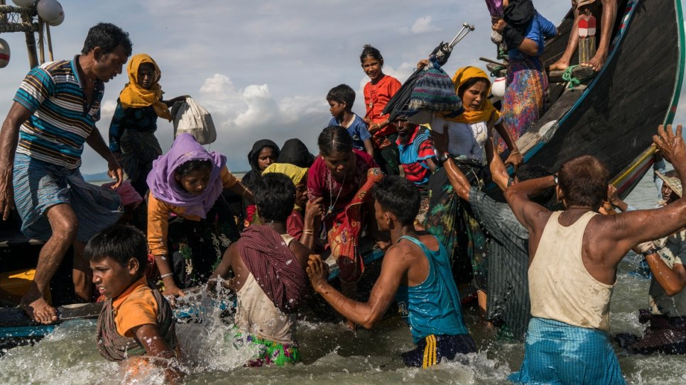 Rohingya refugees scramble off a boat arriving in Bangladesh from Myanmar as it lands on a beach in Dakhinpara, Bangladesh, on September 14 2017.