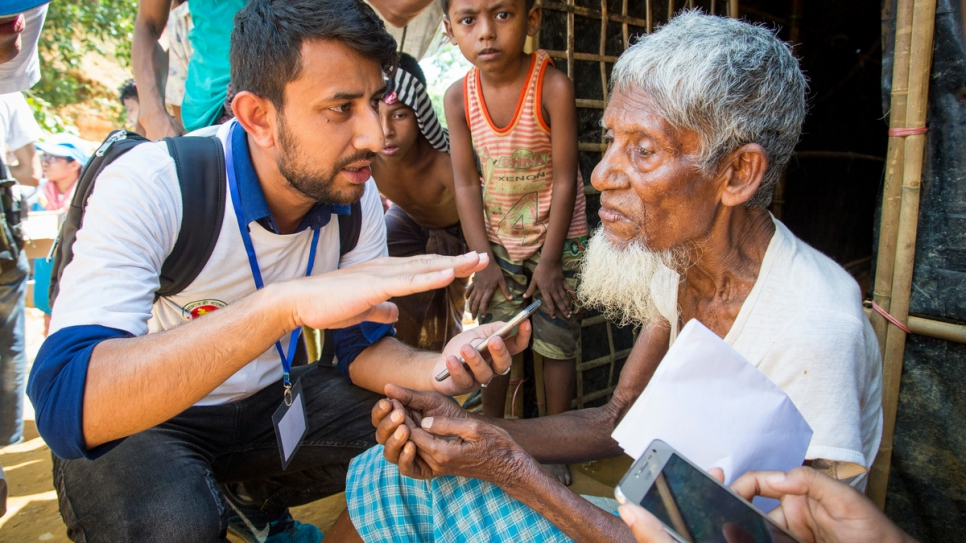 A UNHCR volunteer collects information from Mohammad Busho, 80, in Kutupalong Camp Extension, Bangladesh. The data helps speed assistance to refugee families in need.