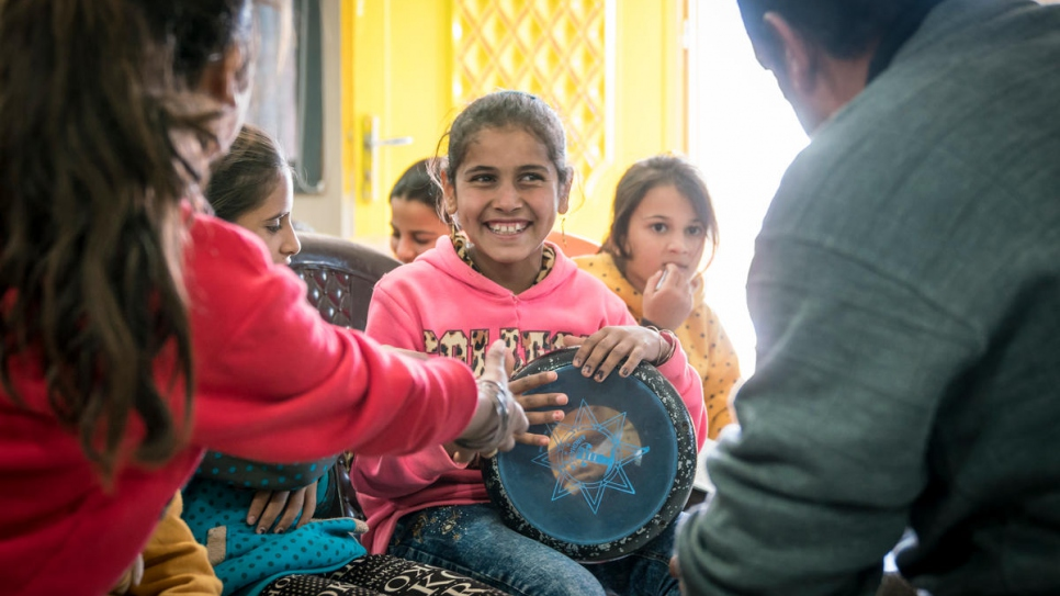 Syrian refugee Ehsan Al Khalili teaches music to a group of children in a UNHCR-funded community centre in Azraq refugee camp, Jordan.