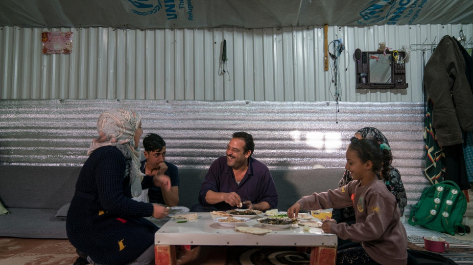 Ehsan Al Khalili, his wife Rabab and three of their children eat lunch in their shelter in Jordan's Azraq refugee camp.
