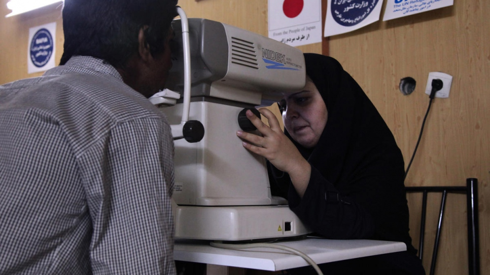 An Afghan refugee undergoes an eye examination at a health centre in Iran.