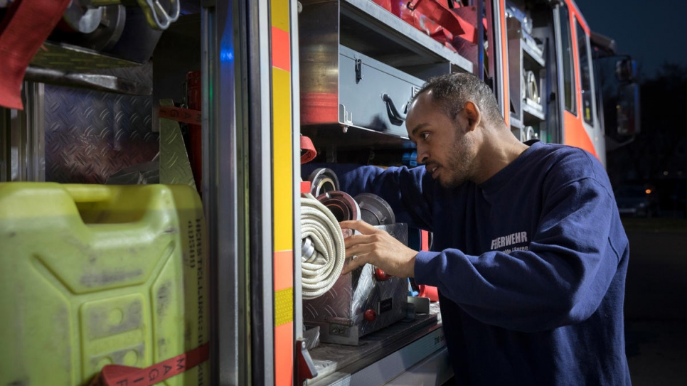 Yusuf checks the equipment on a fire truck. Volunteer firefighters like him come to the station in Fürstenwalde for training once a week.