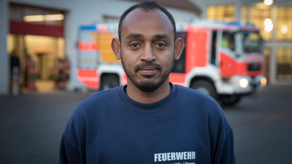 Yusuf, 37, stands in front of the fire station in the town of Fürstenwalde, eastern Germany where he has recently joined as a volunteer.