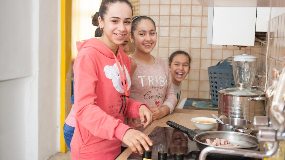 The Al-Bashawat daughters, Hadeel (left), 15, Fatima (partially obscured), 10, Amneh (centre), 13, and Amal (right), 8, make breakfast at home in Vienna, after completing the reunification process.