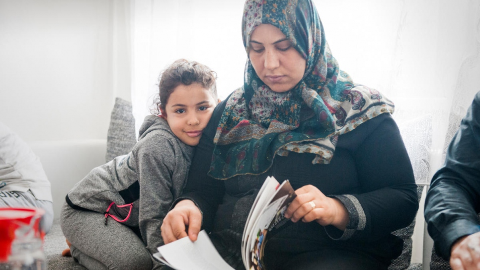 Hayat Elwees and her six-year-old daughter Maryam read a book at home in Vienna, after completing the reunification process.
