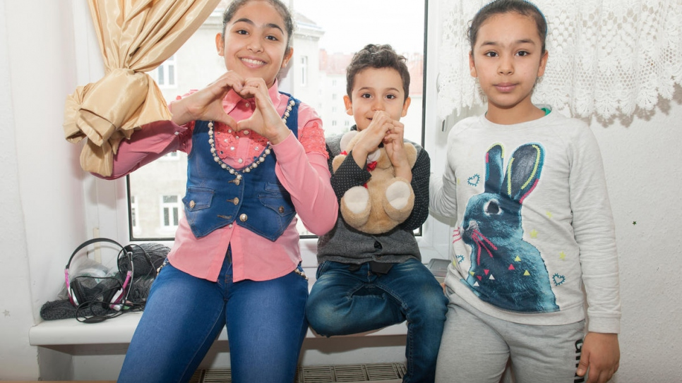 Three of the Al-Bashawat siblings (from left) Fatima, Ali and Amal settle in to their new home, after being reunited with their father in Vienna.