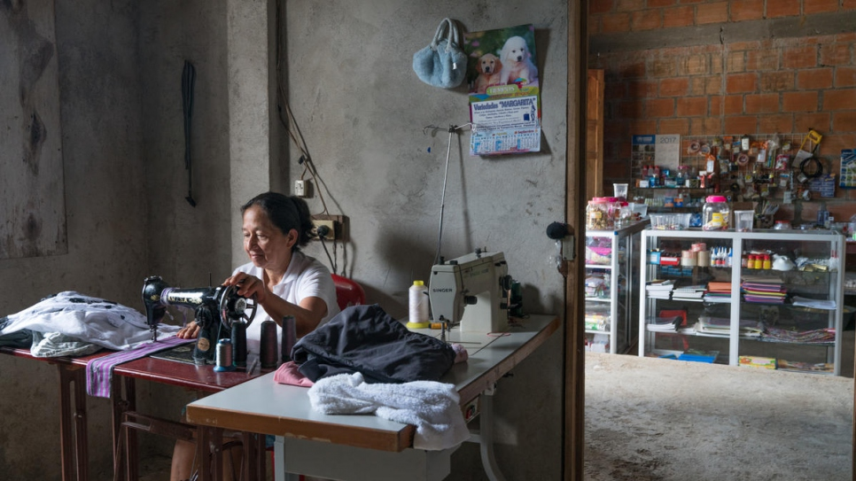Alba Pinto works in her house in Nueva Esperanza. Since fleeing to the settlement she has saved and worked hard to open a shop here where she sells school supplies and other items.