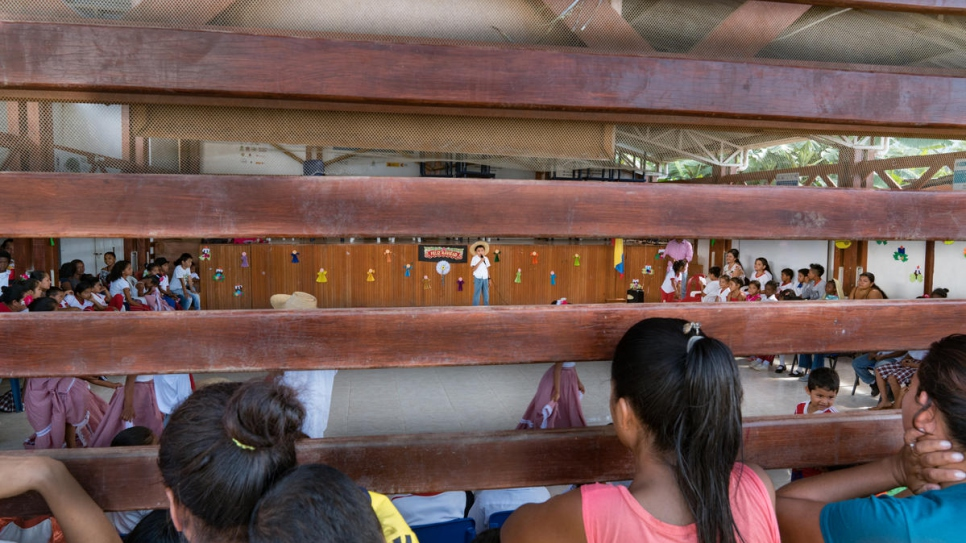 Children watch a student perform during a Christmas show at the school gymnasium in Nueva Esperanza. The events help give a sense of community to the children of displaced families.