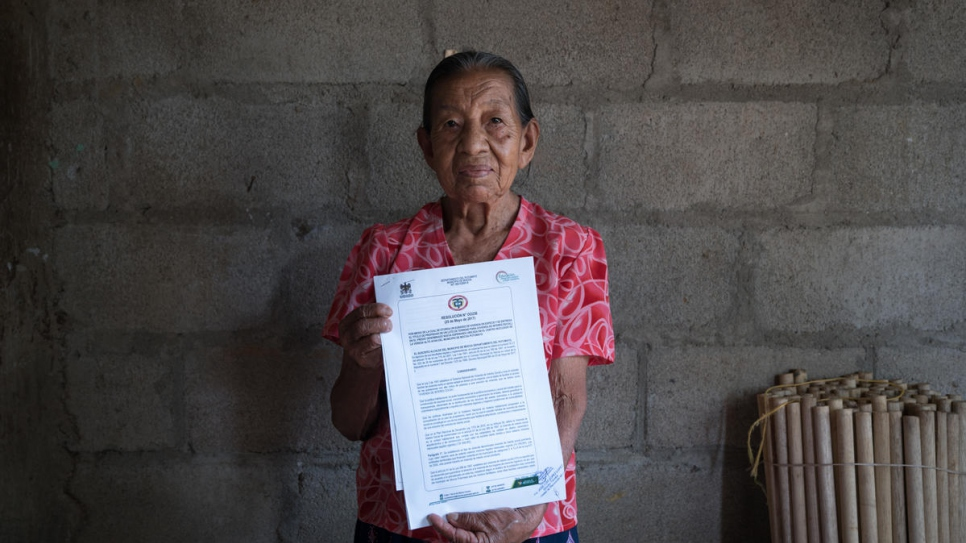 Blanca Elisa Pinto, 84, poses with the home title she received in August, 2017. After six years of lobbying, Nueva Esperanza became the first informal settlement to be legalized in Colombia's Putumayo region.