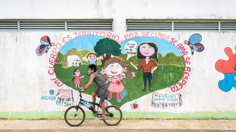 A child rides past a mural with a message of peace in the community of Nueva Esperanza, which is home to 228 families displaced by Colombia's armed conflict.