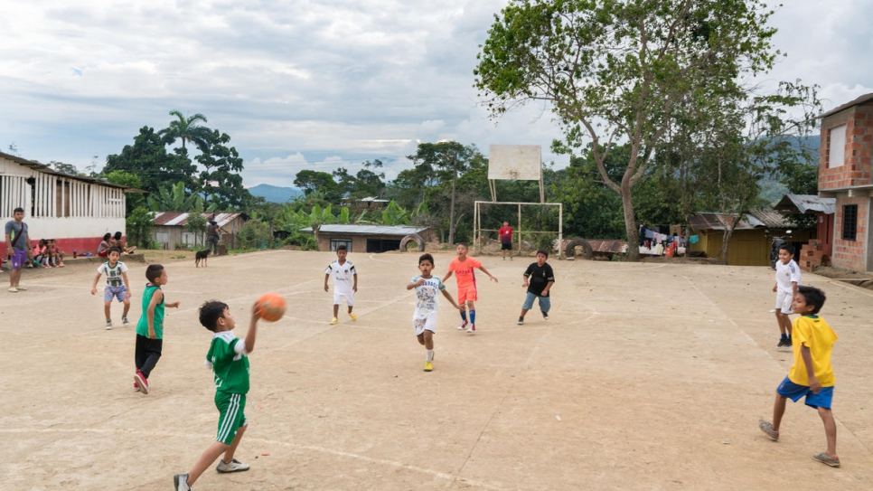 Children play football at Nueva Esperanza's school playground. The settlement's only school has 123 students enrolled in its classes.