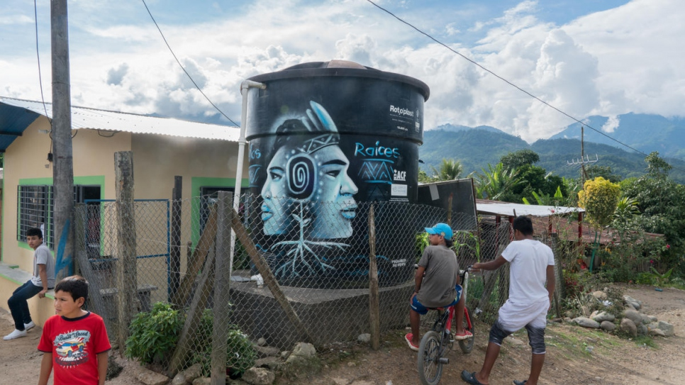 Children stand next to a water tank at the entrance to Nueva Esperanza. The tank, which provides clean water to the community, was installed with the aid of UNHCR in 2016.