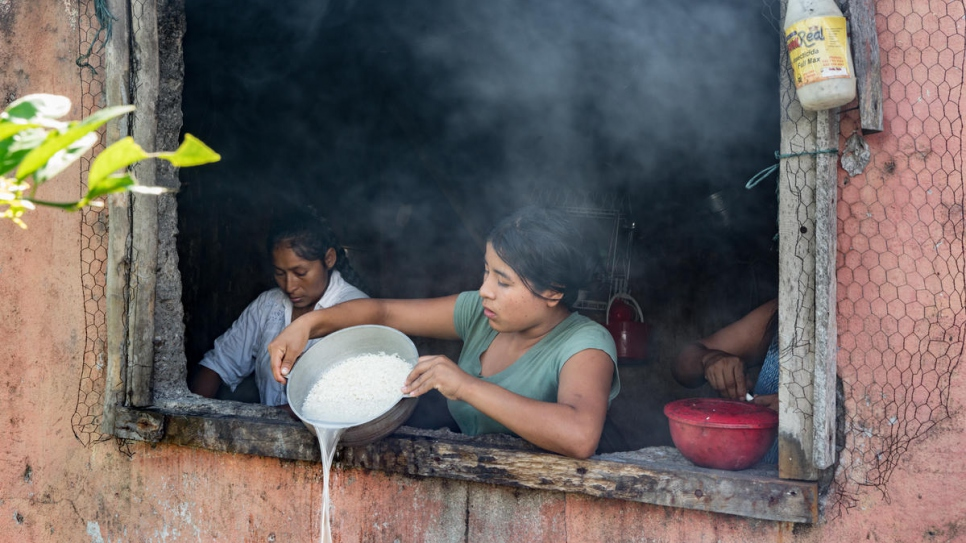 Aida Johana, 19, cooks lunch for her family at Armando Pai's home. As the community leader, Armando is the only resident with a functional kitchen. Aida along with the other 16 families live in shacks with plastic bag roofing.