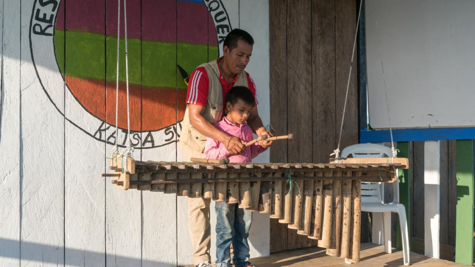 Armando Cuasaluzan Pai, 38, teaches his nephew how to play the marimba - a percussion instrument built from bamboo and traditional to the Awá culture.