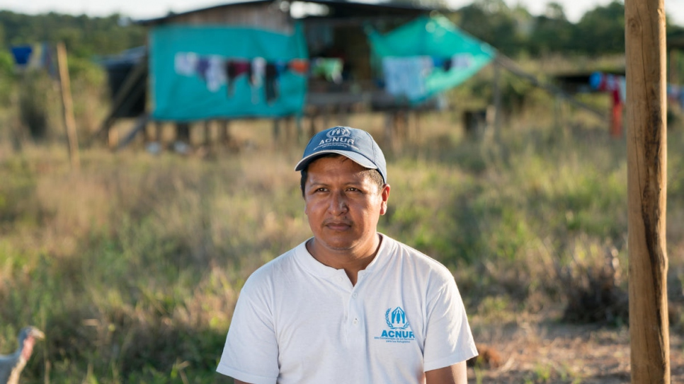 UNHCR officer Harold Juajibioy Otero sits in front of a families' home at Villagarzón's Awá settlement. The UN Refugee Agency supports community empowerment and the reconstruction of indigenous territory.