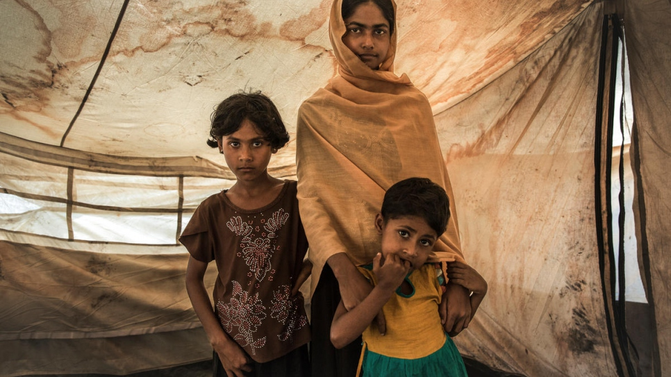 Rabiaa Khatun and her nieces, Umme Salma, 8, and Noor Kalima, 4, stand inside a shelter at a transit camp near Kutupalong camp in Bangladesh.