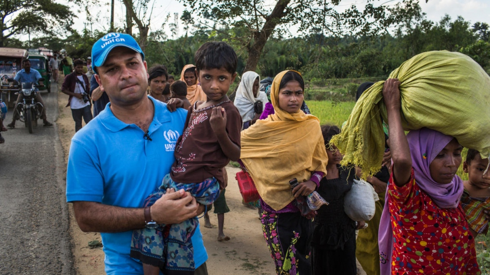 UNHCR spokesman Mohammed Abu Asaker carries Noor Kalima, 4, on the 10-kilometre walk from Myanmar to Kutupalong refugee settlement in Bangladesh. Noor's parents were killed when their village was attacked. Both she and her sister, Umme Salma (wearing black), are being cared for by their aunt, Rabiaa Khatun (wearing orange headscarf).