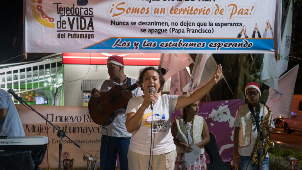 "Fatima Muriel addresses the audience at a community event for ""Dia de las Velitas"" or ""Little Candles Day"", a traditional holiday in Colombia."