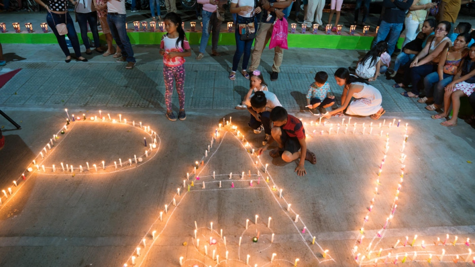 "Women and children light candles forming the word ""paz"" (""peace"") at a community event organized by the Life Weavers Women's Alliance in Mocoa, Colombia."