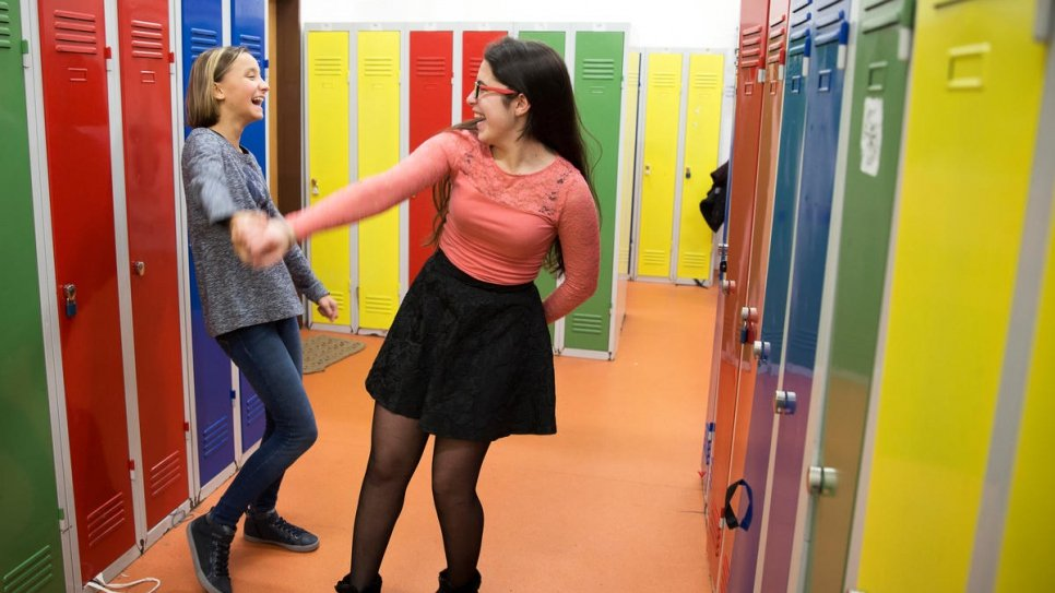 Fourteen-year-old Syrian refugee Natalia Rami Haddad (right) dances with her Czech friend, Natalie Sembdnerova, 12, in the corridors of their school.