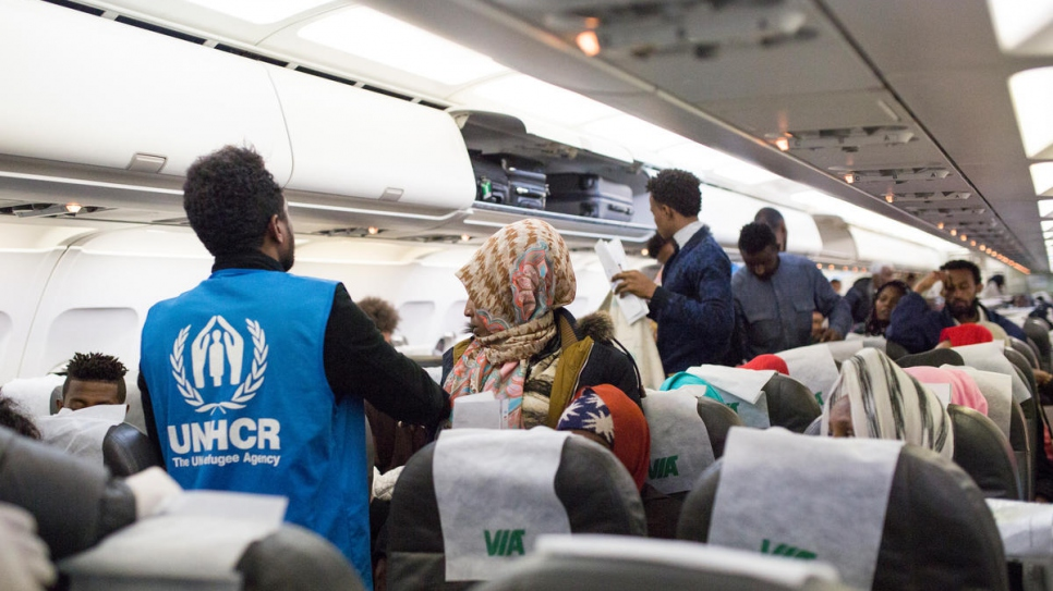 UNHCR staff assist vulnerable refugees as they leave the plane.